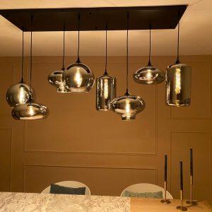 Glazen hanglampen Evy zijn helemaal van deze tijd. Wil je een echte moderne look volgens de trend van dit jaar, dan hebben we een heel nieuw aanbod aan glazen hanglampen voor je. Deze glazen hanglampen zijn gemaakt van stoere materialen zoals smoke glas. De glazen kelken zijn afzonderlijk in hoogte verstelbaar zodat je je eigen persoonlijke sfeer creëert. De 8 kelken bestaan uit een paar verschillende glazen. De kelken zorgen voor een zachte lichtval, daarbij blijft het zicht op de lamp door het grijze glazen oppervlak relatief vrij, waardoor deze stijlvol gekozen moet worden. Vanwege de doorzichtigheid van de bollen is het raadzaam om vintage kooldraad of gloeilampen te kiezen voor een stijlvolle uitstraling. Extra informatie: – De plafondplaat is rechthoekig (140x40cm) – Artikel is dimbaar (niet meegeleverd) – 8 x E27 fitting – Ook andere modellen in de reeks Evy verkrijgbaar met 3 bollen of met een rechte plaat met 6 bollen Deel de foto van je Evy hanglamp op onze social media: Facebook en Instagram